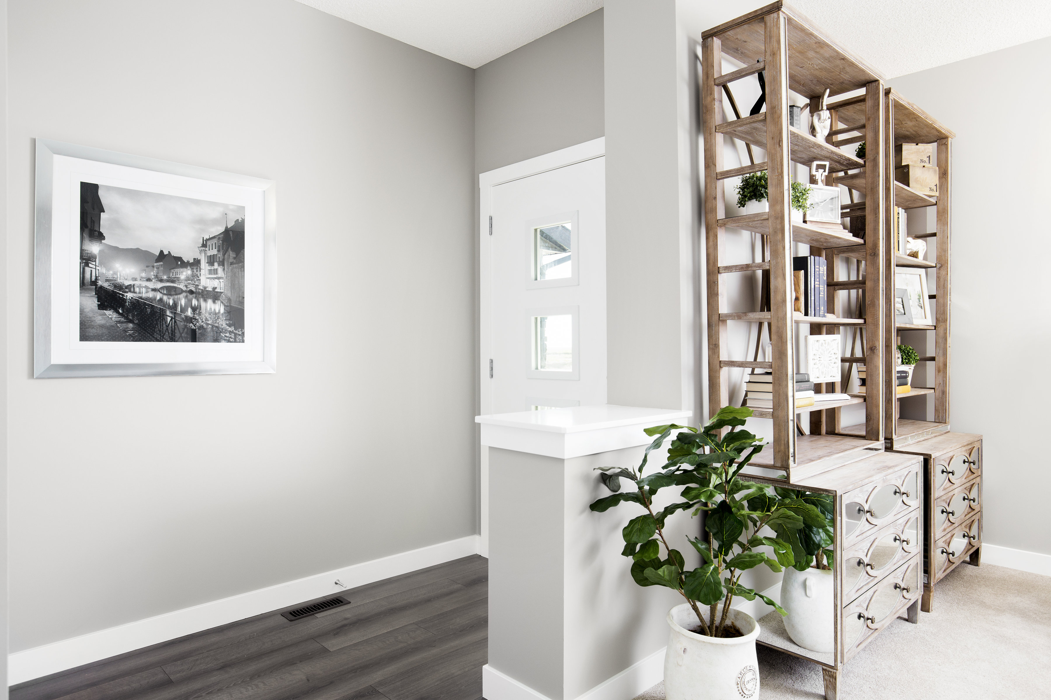 shane homes duplex showhome front entrance with bookshelf and plant.