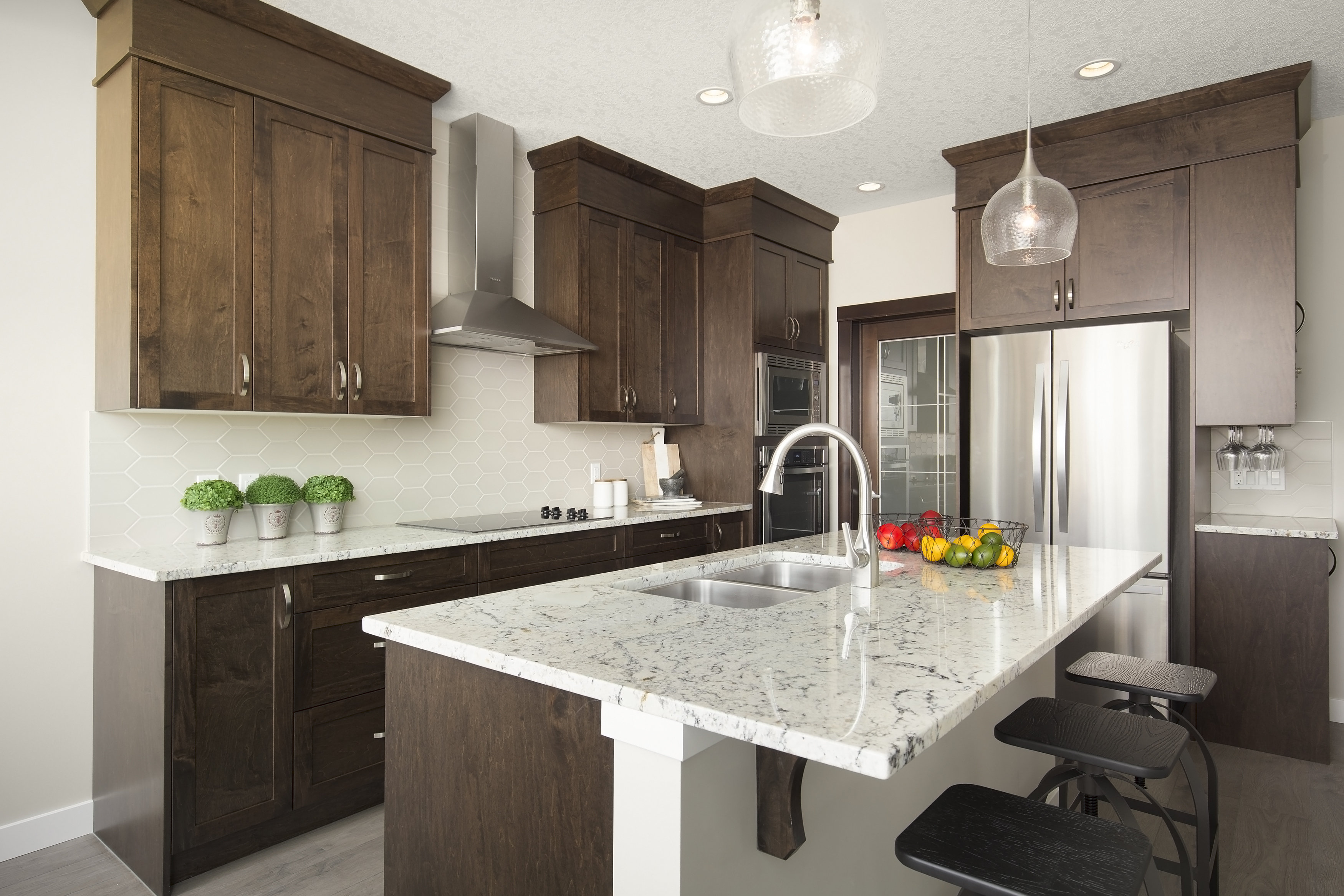 example kitchen with marble counter top and wood cabinets in a shane front drive home.