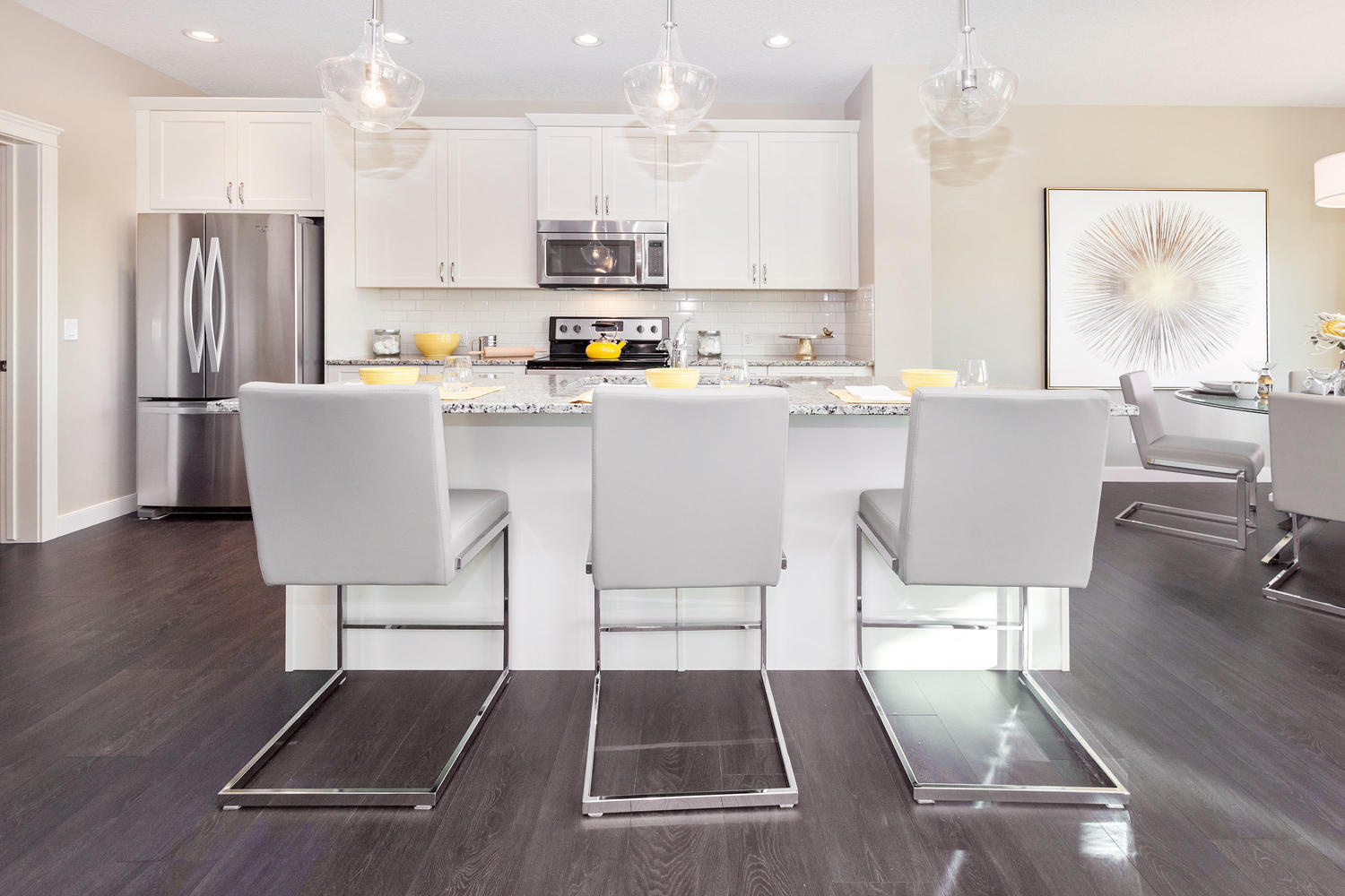 grey bar stools at a large kitchen island in a pacesetter front drive show home.