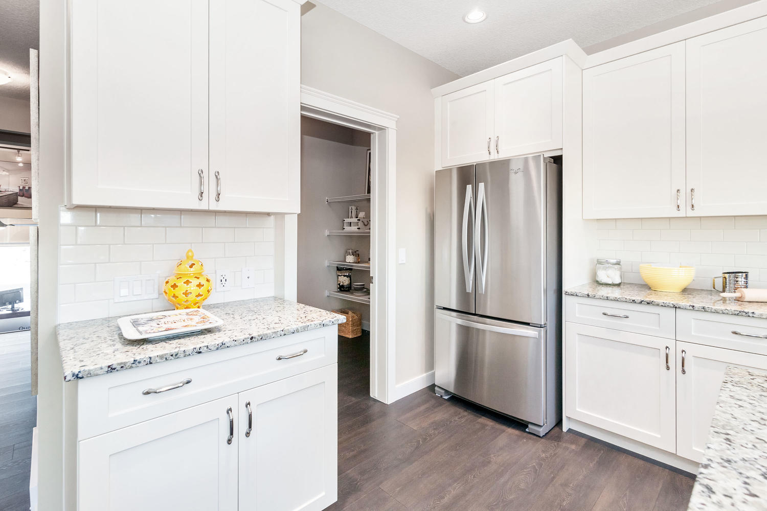double door fridge and walk in pantry in the kitchen of the pacesetter front drive show home.