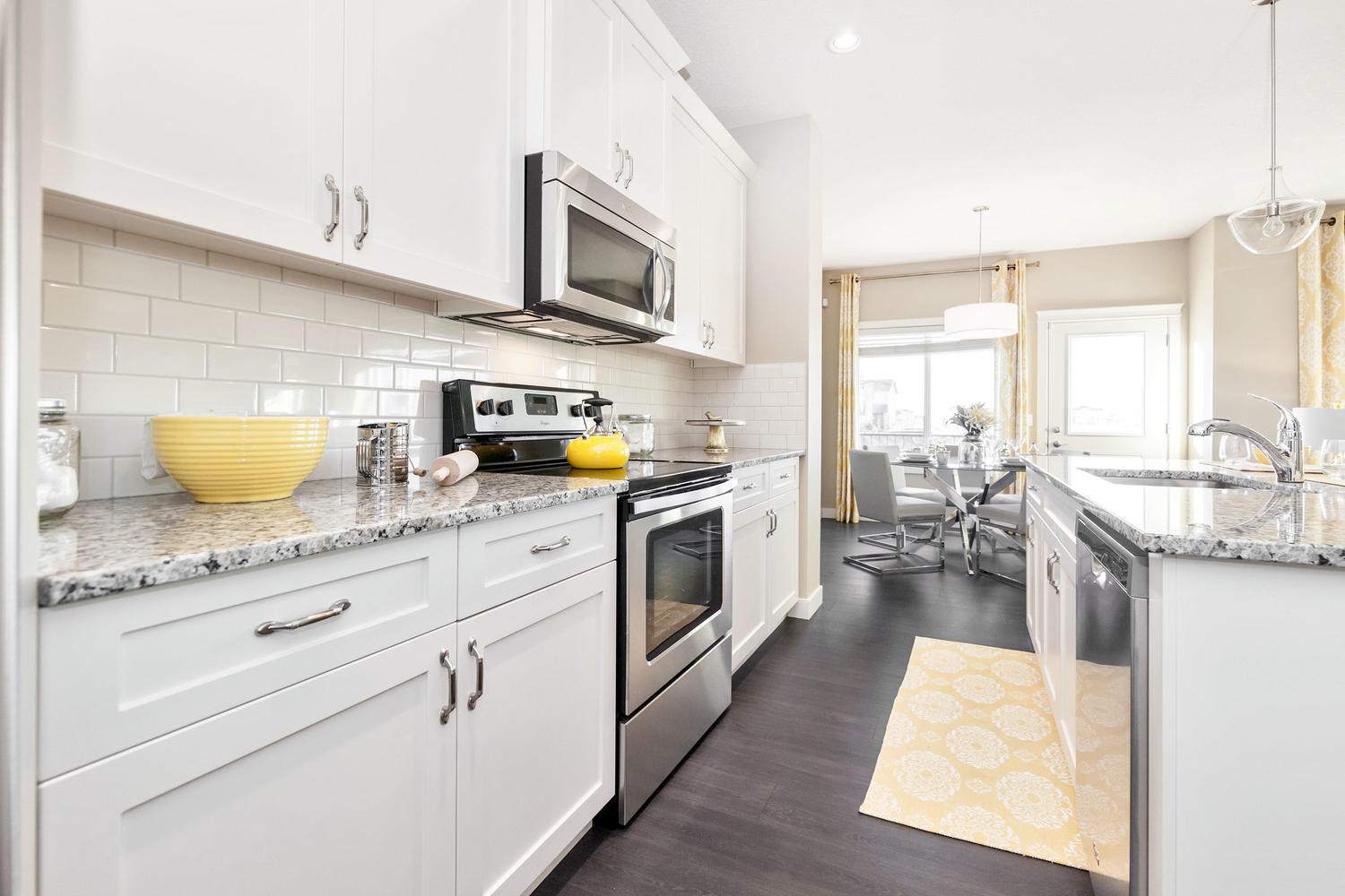 open concept kitchens with white cupboards and yellow accent in pacesetter front drive show home.