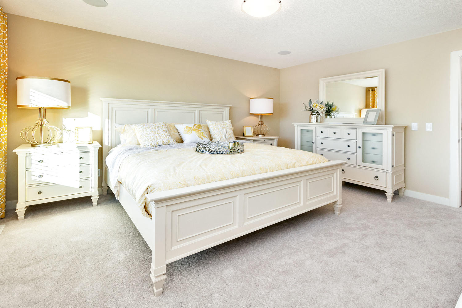 master bedroom with white bedroom furniture of a pacesetter front drive show home.