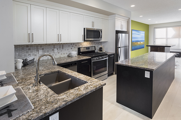 the open kitchen with island in the beckett duplex show home by morrison homes.