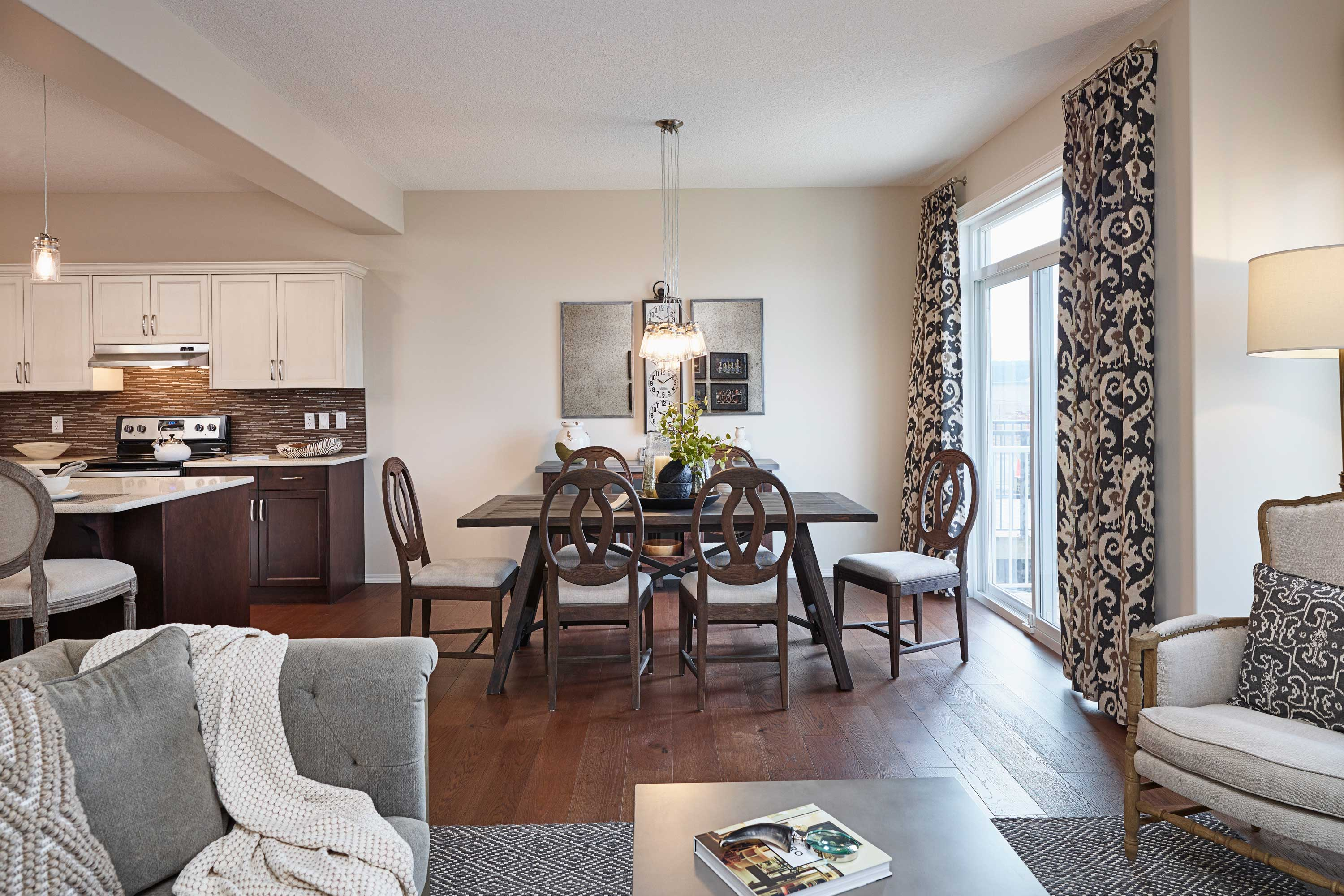 combination living room, dining room, and kitchen beside patio doors in a morrison front drive show home.