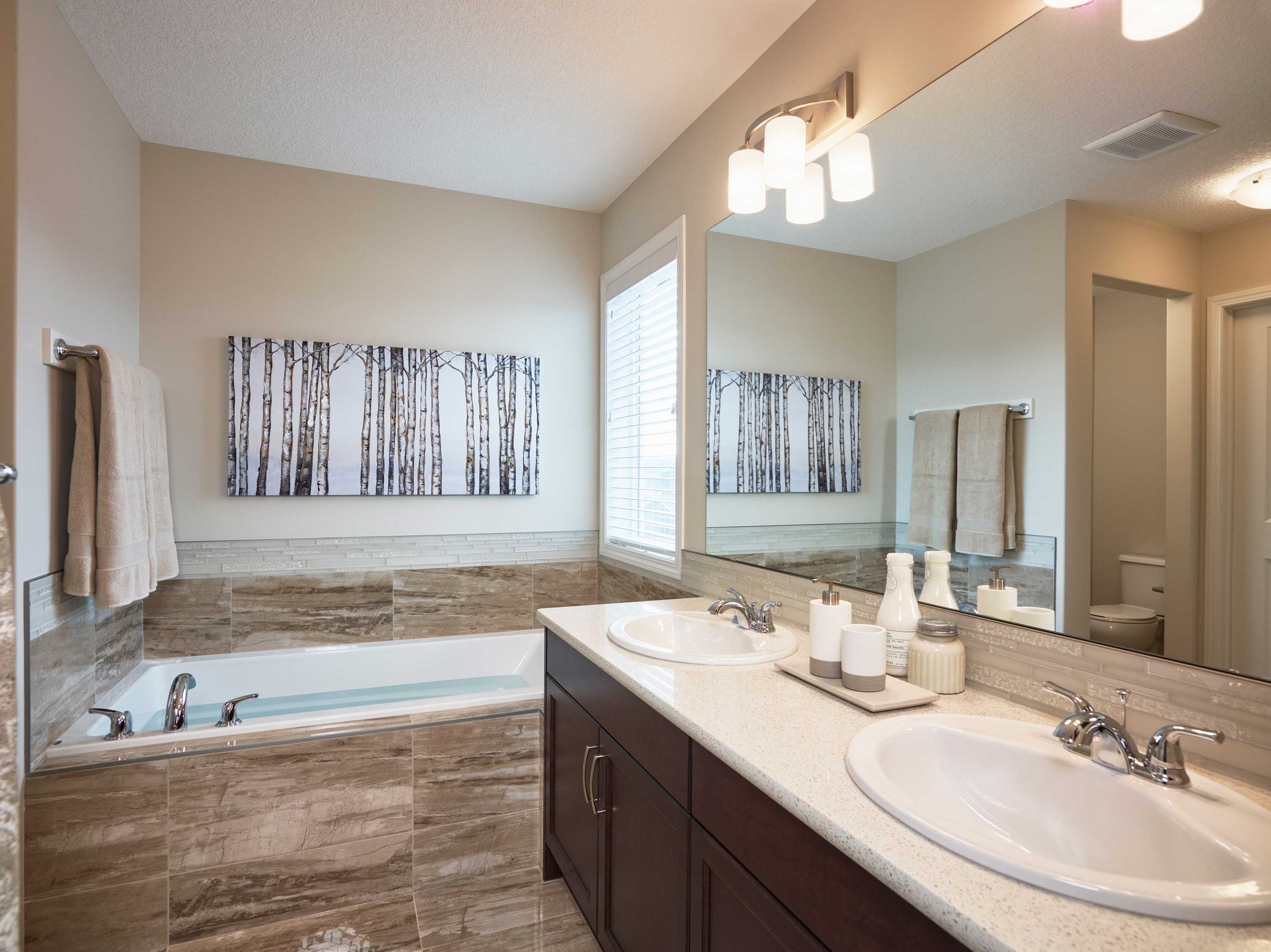 large bathroom with luxury tub and his and her sinks in a morrison front drive show home.