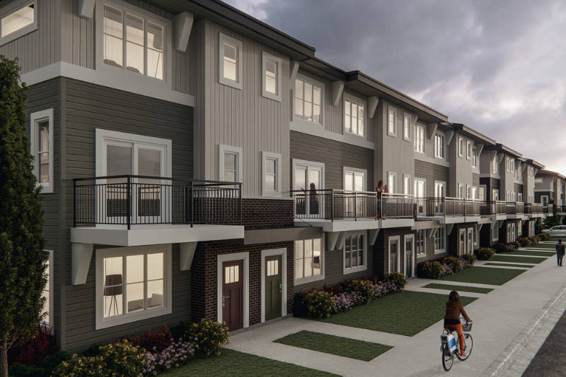 side street view of the yorke townhome's exterior with cyclist on sidewalk.