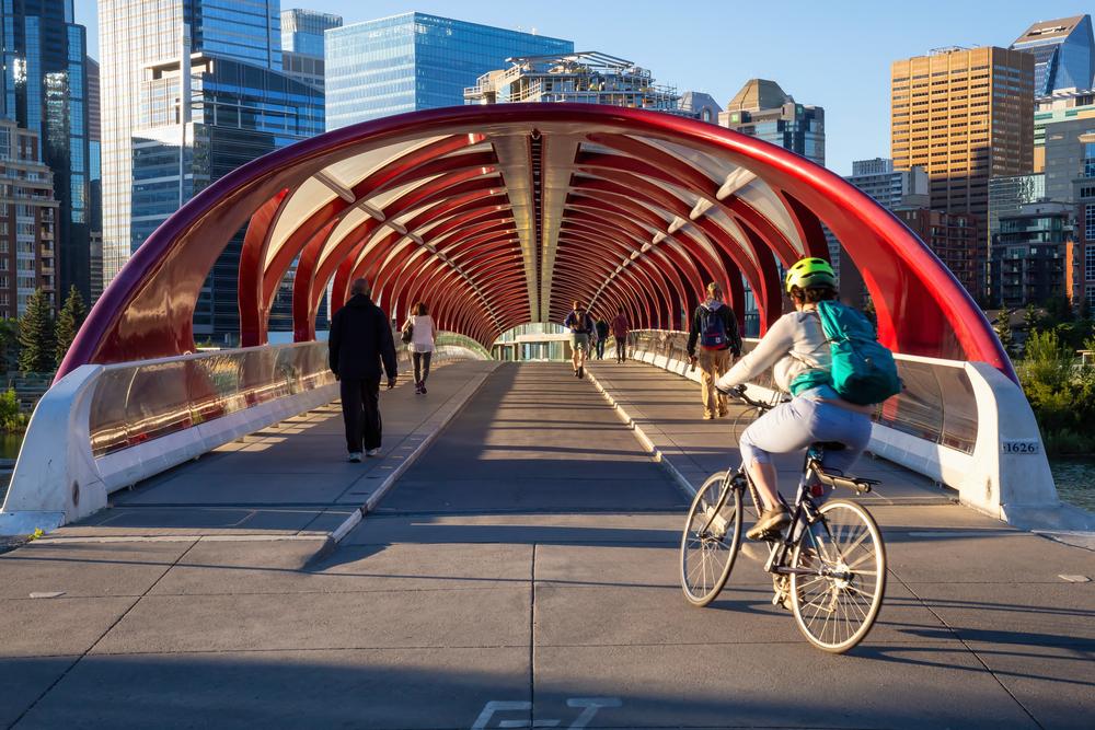 People enjoying the Peace Bridge across Bow River in Calgary, AB