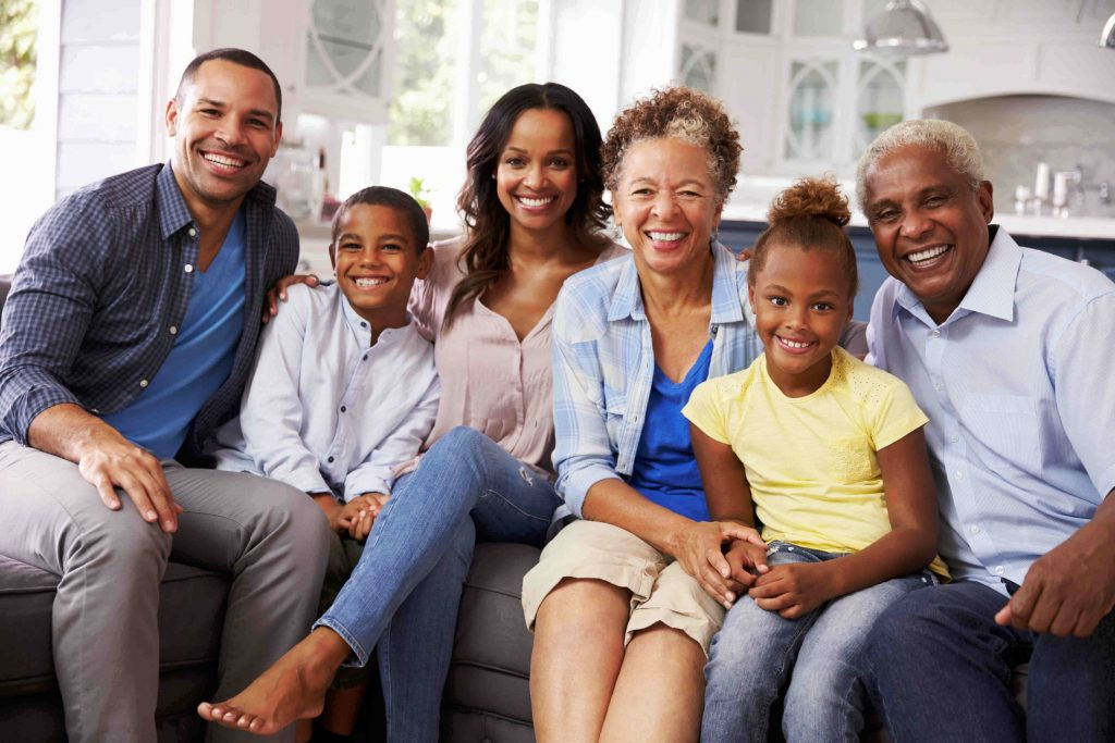 Group portrait of multi-generation black family at home